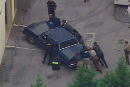 In this view from WJZ-TV video, the car in which two men were arrested at a Maryland roadside rest stop early Thursday, Oct. 24, 2002, is pushed into a facility in Rockville, Md, after being transported from the rest area.  The two were wanted for questioning in the three-week wave of deadly sniper attacks that have terrorized the Washington, D.C. area. (AP Photo/courtesy WJZ-TV)