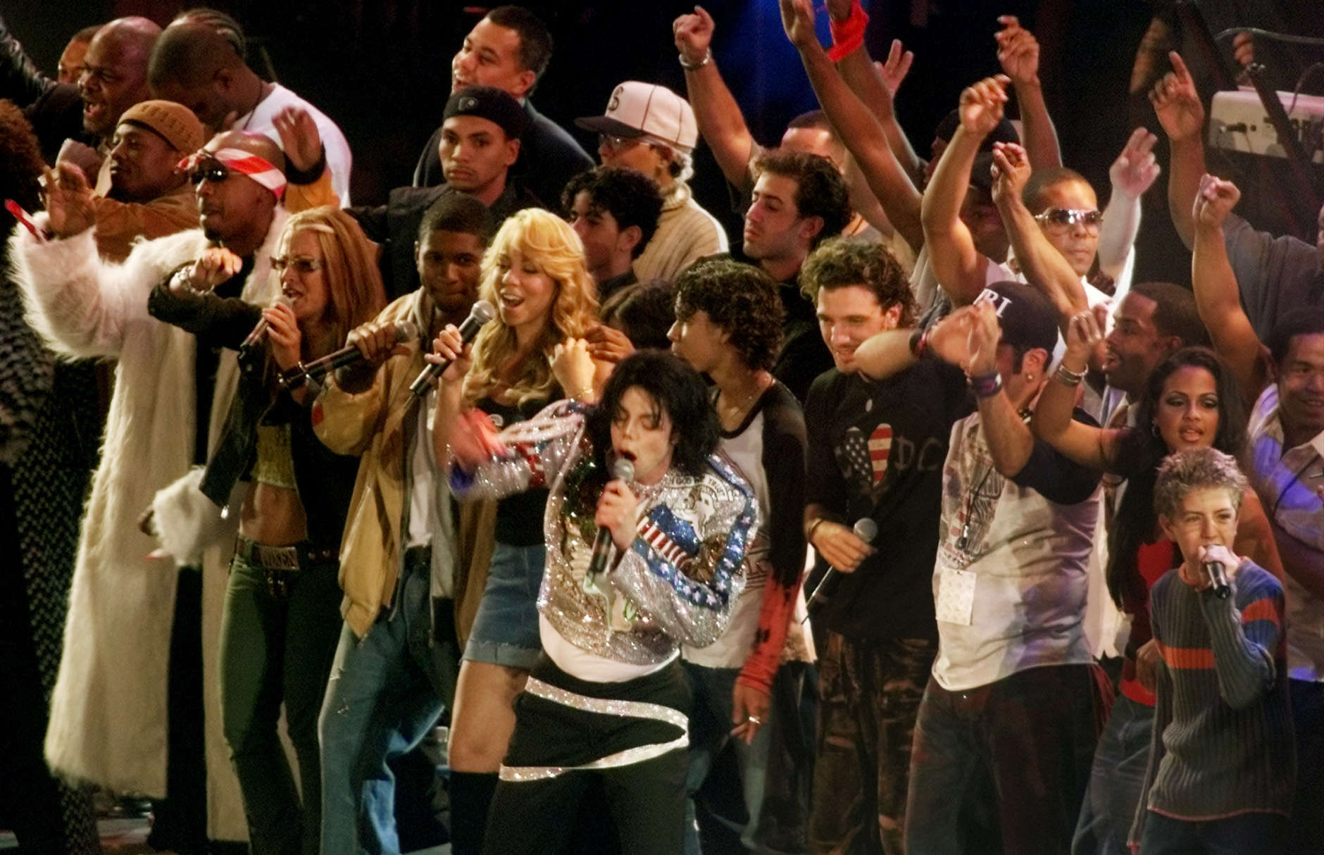 "Michael Jackson, center, is joined by the featured performers of  ""United We Stand: What More Can I Give?"" benefit concert during the finale Sunday, Oct. 21, 2001, at RFK Stadium in Washington. Tens of thousands of music fans gathered Sunday to see an array of pop stars at the marathon concert celebrating America and raising money for victims of September's terrorist attacks. (AP Photo/Pablo Martinez Monsivais)"