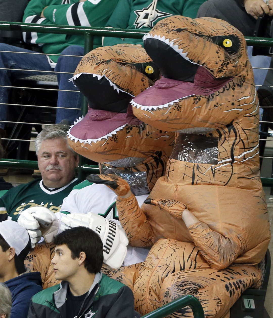 A Dallas Stars fan, left, watches two fans dressed in dinosaur costumes cheer during the third period of the Stars' NHL hockey game against the Washington Capitals on Saturday, Jan. 21, 2017, in Dallas. (AP Photo/Tony Gutierrez)