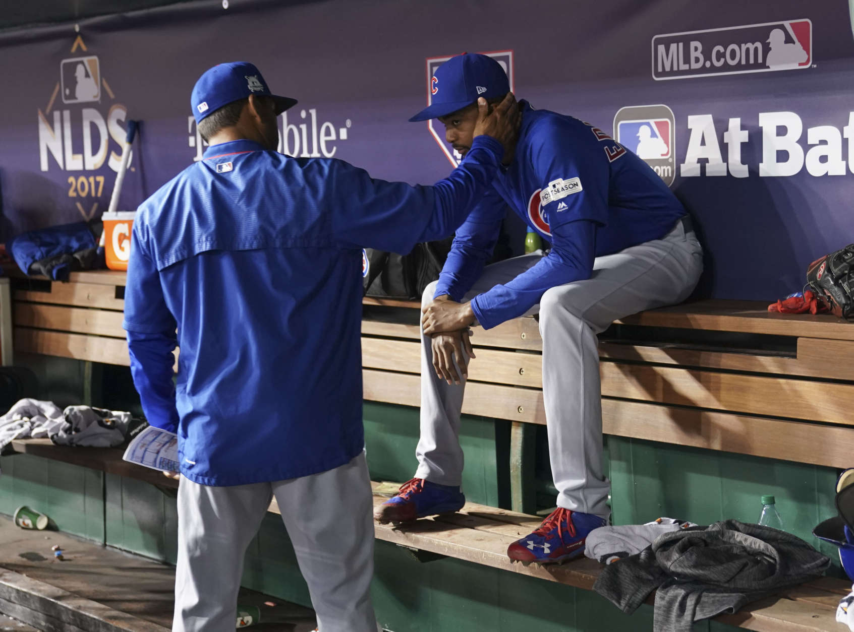 Chicago Cubs bench coach Dave Martinez, left, consoles Chicago Cubs relief pitcher Carl Edwards Jr., in the dugout during the seventh inning in Game 5 of baseball's National League Division Series against the Washington Nationals at Nationals Park, Thursday, Oct. 12, 2017, in Washington. (AP Photo/Pablo Martinez Monsivais)