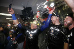 Members of the Chicago Cubs celebrate after Game 5 of baseball's National League Division Series against the Washington Nationals, at Nationals Park, early Friday, Oct. 13, 2017, in Washington. The Cubs won 9-8. (AP Photo/Alex Brandon)