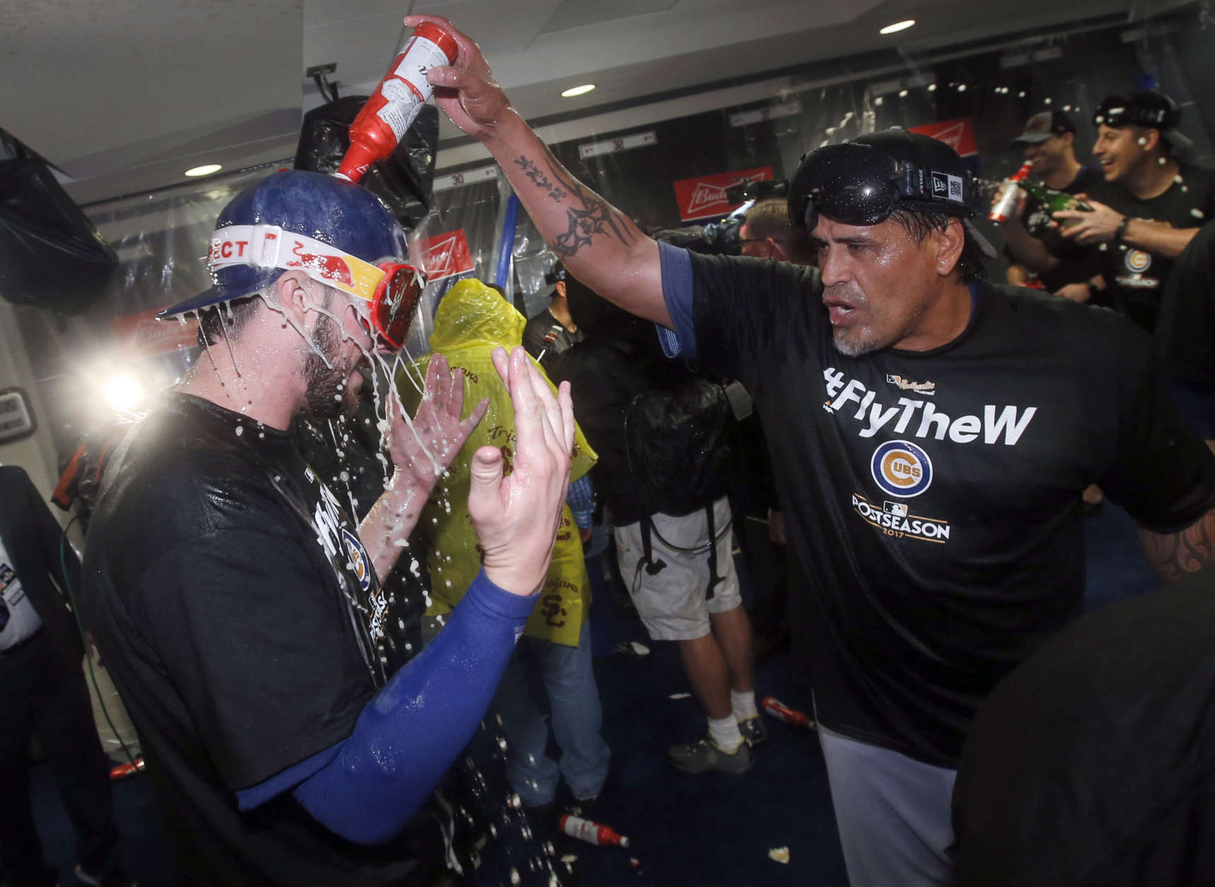 Chicago Cubs' Kris Bryant, left, is doused by Henry Blanco as they celebrate after the Cubs defeated the Washington Nationals 9-8 in Game 5, to win baseball's National League Division Series, at Nationals Park, Friday, Oct. 13, 2017, in Washington.  (AP Photo/Alex Brandon)