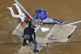 Chicago Cubs catcher Willson Contreras (40) tags out Washington Nationals Trea Turner (7) at home on a infield grounder by Bryce Harper during the first inning of Game 5 of baseball's National League Division Series, at Nationals Park, Thursday, Oct. 12, 2017, in Washington. Behind the plate is umpire Jerry Lane.  The Cubs won 9-8. (AP Photo/Pablo Martinez Monsivais)