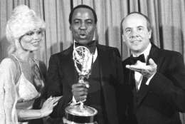 """FILE - In this Sept. 10, 1979 file photo, Robert Guillaume, center, accepts his Emmy Award  for best supporting actor in a comedy-variety or music series for his role in """"Soap"""" from Tim Conway, right, and Loni Anderson at the 31st Emmy Awards in Los Angeles.  Guillaume, who won Emmy Awards for his roles on """"Soap"""" and """"Benson,"""" died Tuesday, Oct. 24, 2017 in Los Angeles at age 89. Guillaume's widow Donna Brown Guillaume says he had been battling prostate cancer. (AP Photo/Reed Saxon, File)"""