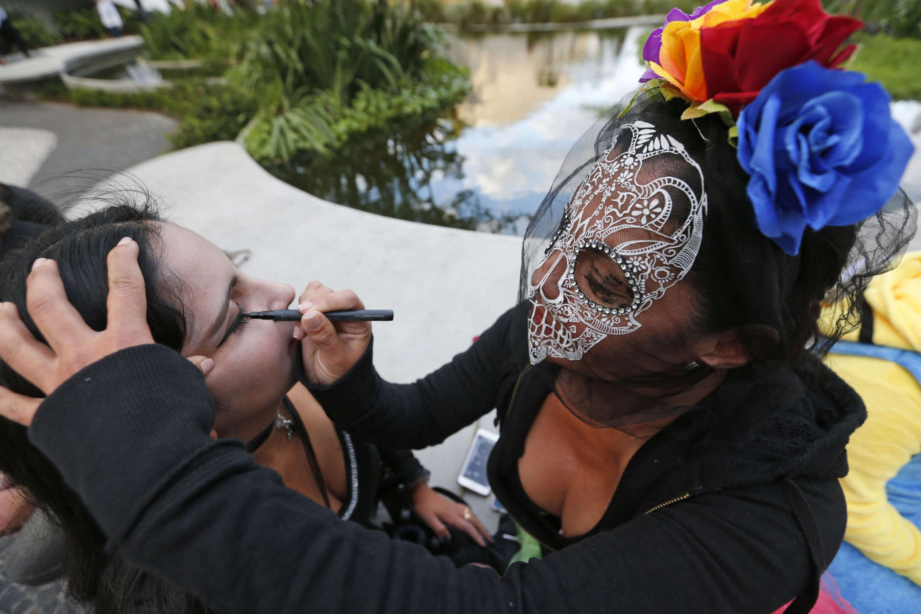 Cristina Ramirez, right, helps Alcira Tabon paint her face as they prepare to stroll along the Lincoln Road pedestrian mall for Halloween, Tuesday, Oct. 31, 2017, in the South Beach neighborhood of Miami Beach, Fla. (AP Photo/Wilfredo Lee)