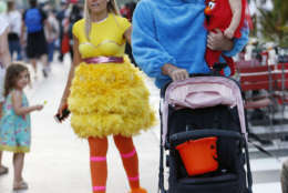 Josh Keller, center, walks with his daughter Isabel, 1, and his wife Laura as they trick-or-treat dressed up as Big Bird, Cookie Monster and Elmo along the Lincoln Road pedestrian mall for Halloween, Tuesday, Oct. 31, 2017, in the South Beach neighborhood of Miami Beach, Fla. (AP Photo/Wilfredo Lee)