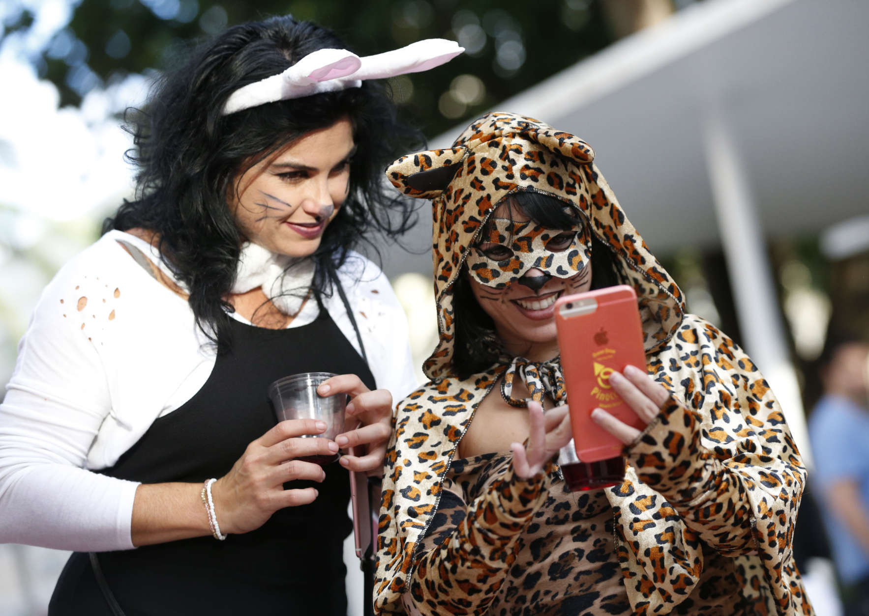 Annabel Sanchez, left, and Grety Artiles stop to take a selfie as they walk along the Lincoln Road pedestrian mall for Halloween, Tuesday, Oct. 31, 2017, in the South Beach neighborhood of Miami Beach, Fla. (AP Photo/Wilfredo Lee)