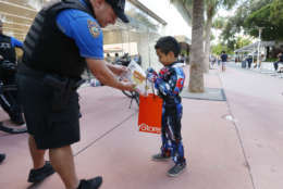 Miami Beach police officer Lee Clair, left, hands out candy to trick-or-treaters like Christopher Rincon, 7, along the Lincoln Road pedestrian mall for Halloween, Tuesday, Oct. 31, 2017, in the South Beach neighborhood of Miami Beach, Fla. (AP Photo/Wilfredo Lee)