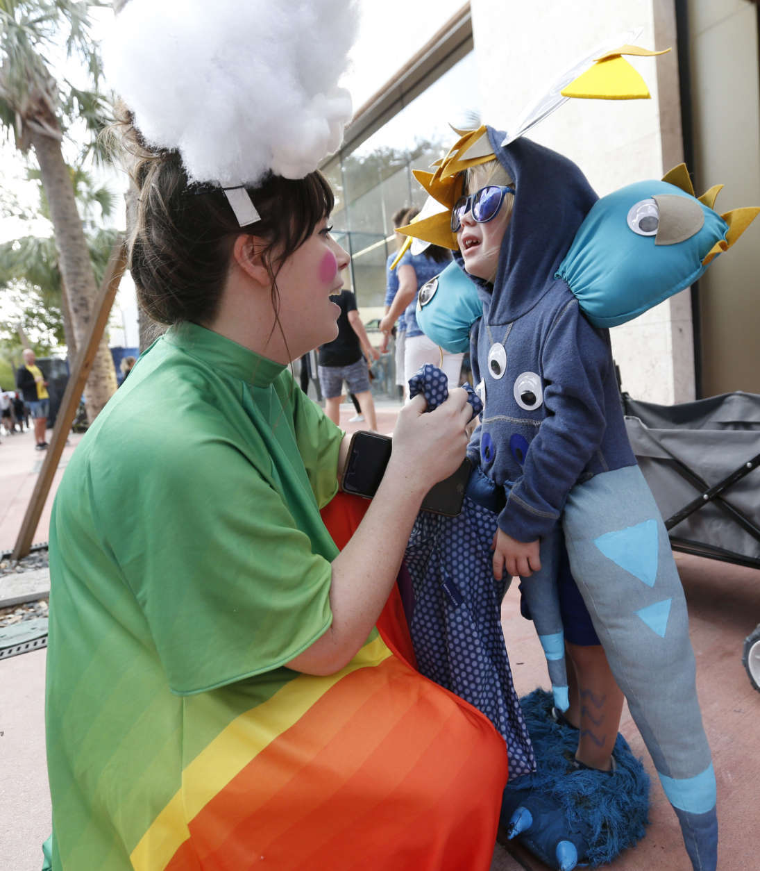 Dressed as a rainbow, Caroline Sayre helps her son Navy, 3, put on his blue monster costume as they prepare to trick-or-treater along the Lincoln Road pedestrian mall for Halloween, Tuesday, Oct. 31, 2017, in the South Beach neighborhood of Miami Beach, Fla. (AP Photo/Wilfredo Lee)