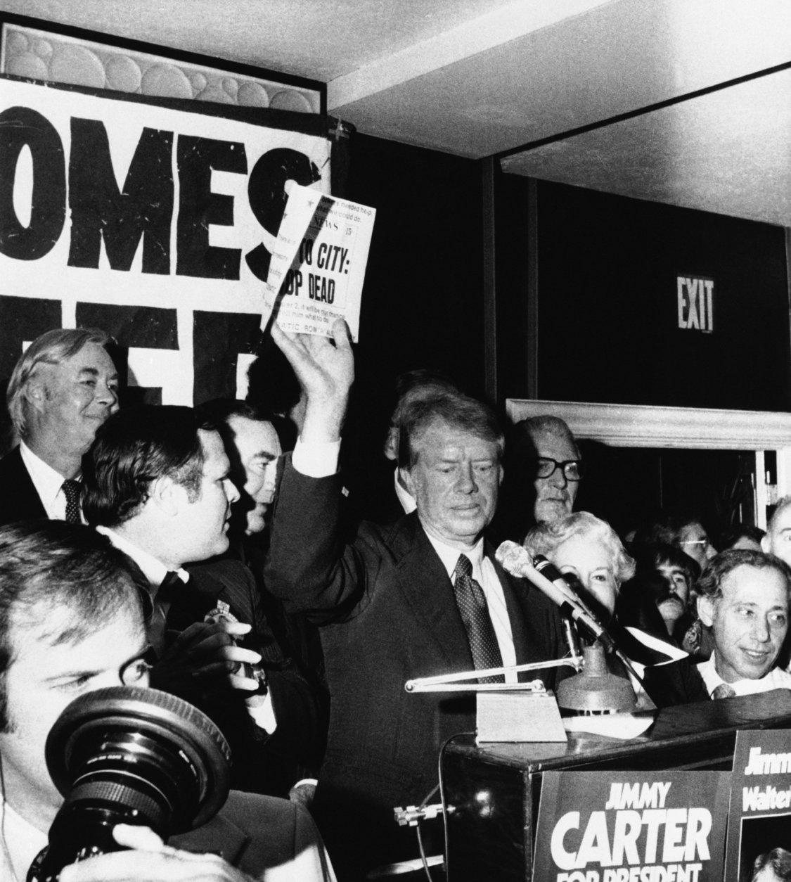 """Democratic presidential nominee Jimmy Carter, center, waves a copy of the New York Daily News carrying a headline """"Ford to City: Drop Dead"""" during a reception at a Queens, N.Y., restaurant, Oct. 15, 1976. Standing behind the former Georgia governor are, from left: state Democratic nominee for U.S Senate, Daniel Patrick Moynihan, Queens borough President Donald Manes and Gov. Hugh Carey, partially hidden. (AP Photo)"""