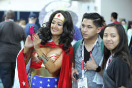 Michelle Camarillo, dressed as Wonder Woman, looks at a selfie on the second day of the 2015 Comic-Con International held at the San Diego Convention Center Friday, July 10, 2015, in San Diego.  The pop-culture event runs July 9-12.  (Photo by Denis Poroy/Invision/AP)