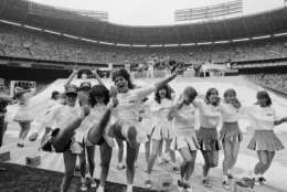 Washington area high school girls, recruited to help set up the stage for the Beach Boys, take to dancing as the Beach Boys perform their opening number at RFK Stadium in Washingto, June 12, 1983. The Beach Boys held their concert after the Team America-Ft. Lauderdale Strikers soccer game. (AP Photo/Ira Schwarz)
