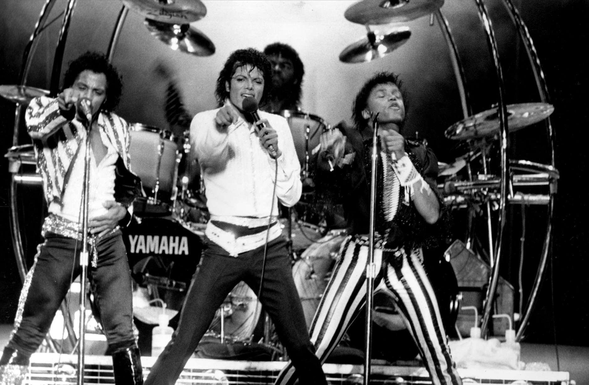 Four of the Jacksons, from left, Tito, Michael, Marlon, on drums, and Randy, are shown performing during their Victory Tour concert at RFK Stadium in Washington, D.C., on Sept. 22, 1984.  (AP Photo/Bill Auth)
