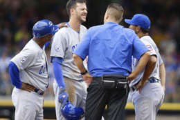 Chicago Cubs' Kris Bryant reacts at second base with third base coach Gary Jones, left a trainer and Dave Martinez, right, after Bryant was injured while sliding into second base during the fifth inning of a baseball game against the Milwaukee Brewers, Sunday, Aug. 2, 2015, in Milwaukee. Bryant was hurt on the play and left the game. (AP Photo/Jeffrey Phelps)