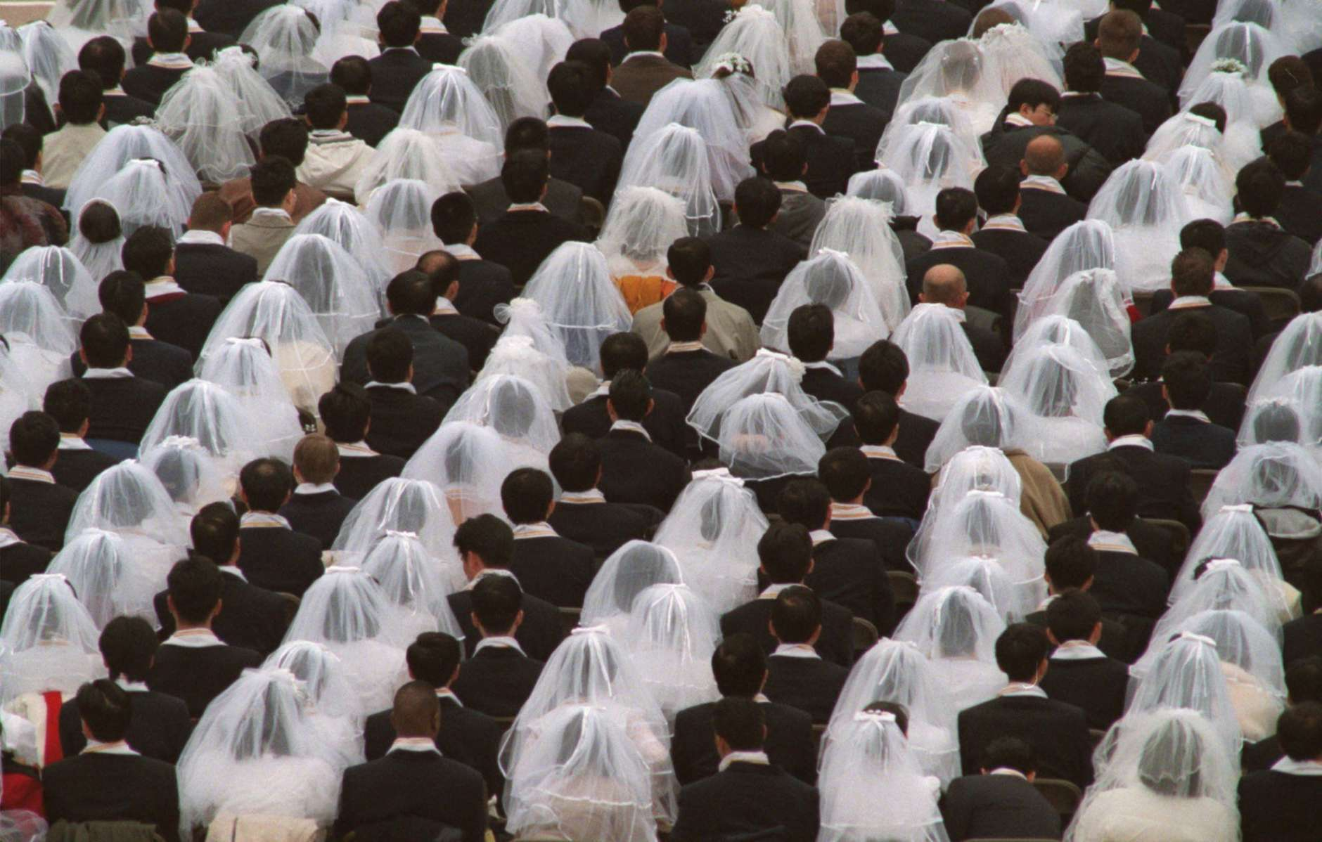 Some of the 28,000 couples participate in a marriage affirmation ceremony officiated by the Rev. and Mrs. Sun Myung Moon, founders of the Unification Church, at RFK Stadium, Saturday, Nov. 29, 1997, in Washington. D.C. (AP Photo/Ken Cedeno)