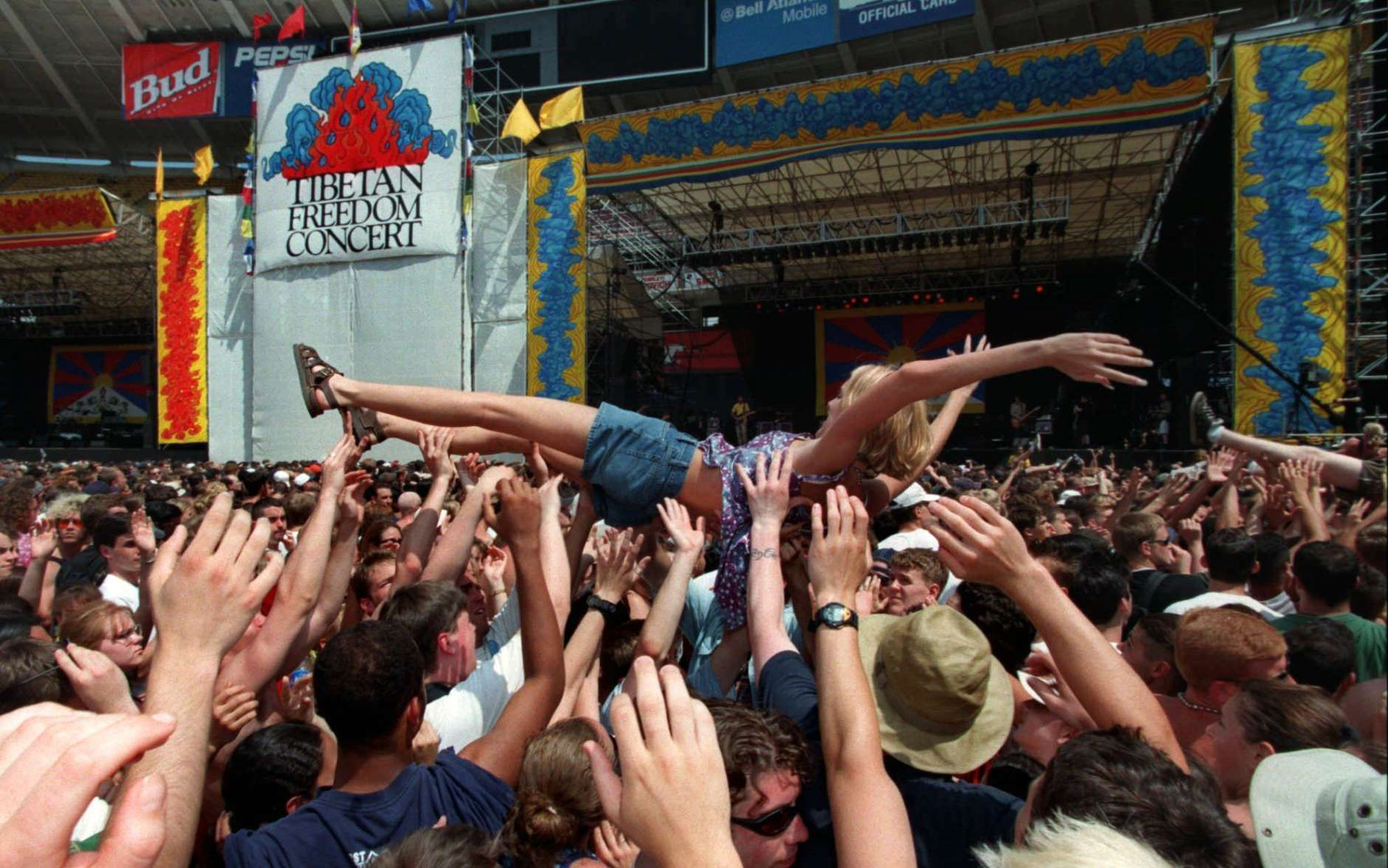 A girl body surfs across the crowd at RFK Stadium in Washington Sunday, June 14, 1998, during the second day of the Tibetan Freedom Festival.  The concert featuring some of the world's top rock bands performed to advocate freedom for Tibet.  (AP Photo/Ken Cedeno)