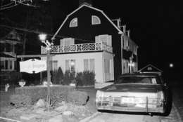 Police and members of the Suffolk County Coroner's Office investigate the murder of six people found shot in Amityville, N.Y., Nov. 14, 1974. The six bodies were from the Ronald DeFeo family and were discovered by another member of the family at early Wednesday evening. (AP Photo/Richard Drew)