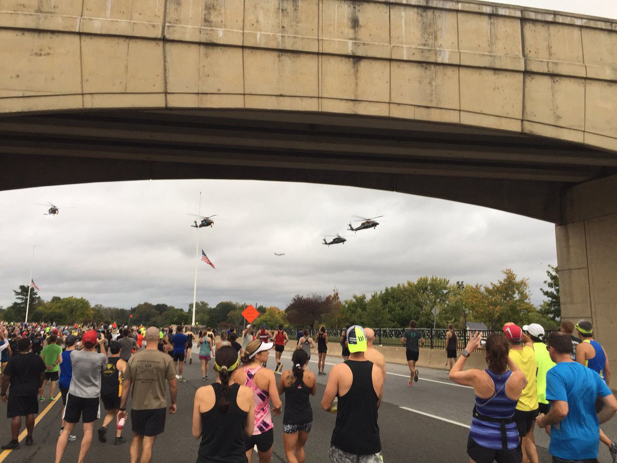 Blackhawk helicopters fly overhead along Route 110 during the Army 10 Miler. (WTOP/John Domen)