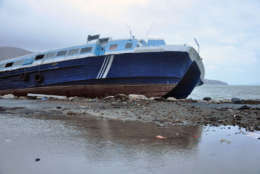 A ferry beached last week by Hurricane Irma in Road Town, Tortola, the capital of the British Virgin Islands, remained unmoved after Hurricane Maria passed, early Wednesday, Sept. 20, 2017. (AP Photo/Freeman Rogers)