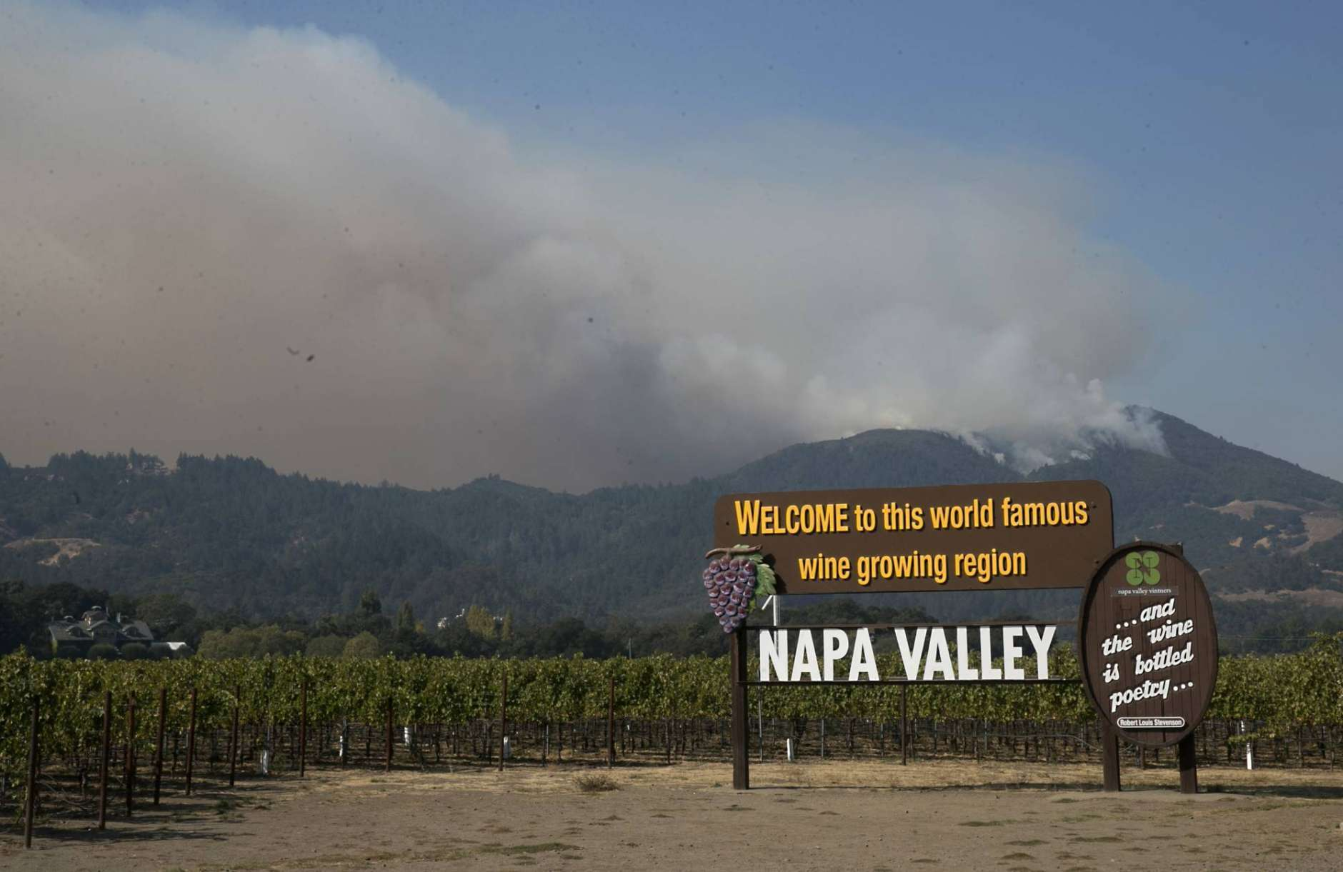 Smoke billows from a fire burning in the mountains over Napa Valley, Friday, Oct. 13, 2017, in Oakville, Calif. Firefighters gained some ground on a blaze burning in the heart of California's wine country but face another tough day ahead with low humidity and high winds expected to return. (AP Photo/Rich Pedroncelli)