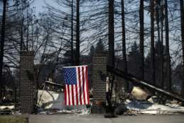 An American flag hangs on a burned home, Sunday, Oct. 15, 2017, in the Coffey Park neighborhood in Santa Rosa, Calif., that was devastated by a wildfire. A state fire spokesman says it appears firefighters are making good progress on deadly wildfires that started a week earlier, devastating wine country and other parts of rural Northern California. (AP Photo/Jae C. Hong)