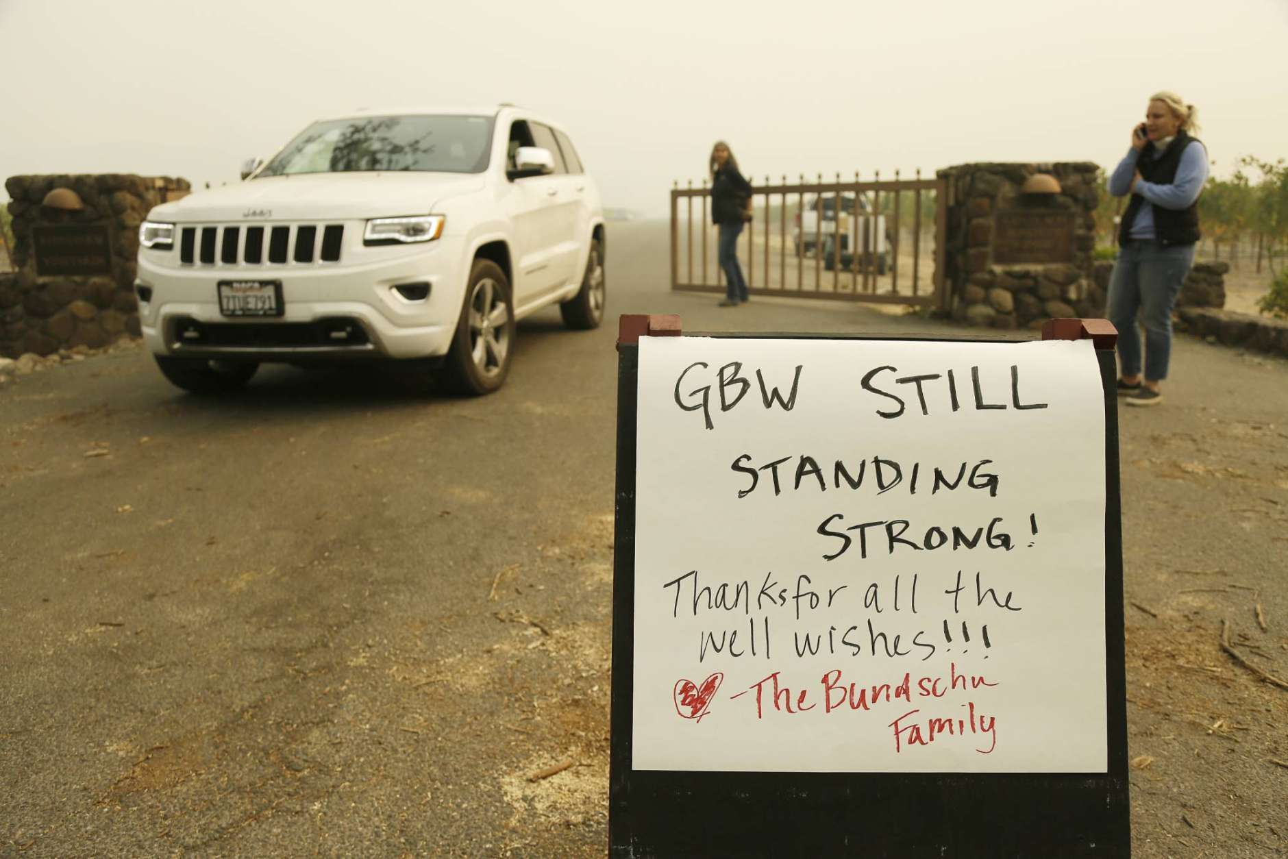 A sign tells people that the historic Gundlach Bundschu winery is still standing, Tuesday, Oct. 10, 2017, in this view near Sonoma, Calif. Workers in Northern California's renowned wine country picked through charred debris and weighed what to do with pricey grapes after wildfires swept through lush vineyards and destroyed at least two wineries and damaged many others. (AP Photo/Eric Risberg)