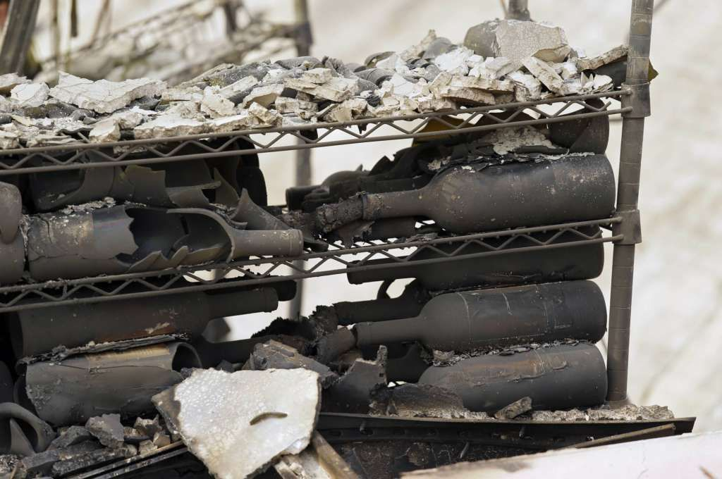 The remains of burned bottles of wine are seen at the Signorello Estate winery Tuesday, Oct. 10, 2017, in Napa, Calif. Worried California vintners surveyed the damage to their vineyards and wineries Tuesday after wildfires swept through several counties whose famous names have become synonymous with fine food and drink. (AP Photo/Eric Risberg)