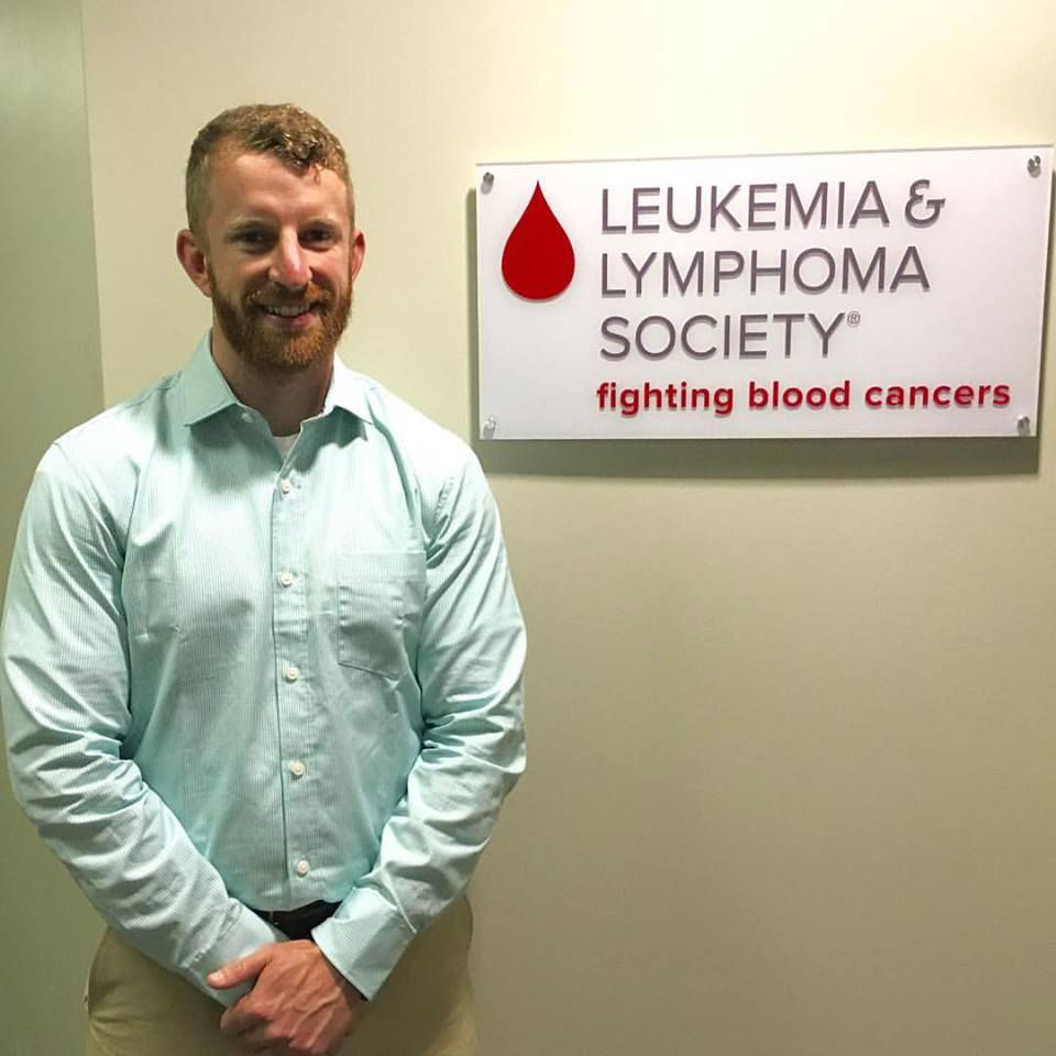 A picture of of Vincent Carrano in front of the Leukemia & Lymphoma Society sign on his first day of work for the organization on April 18, 2016. (Courtesy Vincent Carrano)