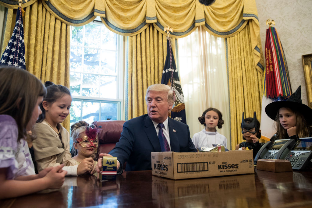 WASHINGTON, DC - OCTOBER 27: U.S. President Donald Trump hands out Halloween candy to children of journalists and White House staffers in the Oval Office at the White House, October 27, 2017 in Washington, DC. The children were dressed in costume for Halloween.  (Drew Angerer/Getty Images)