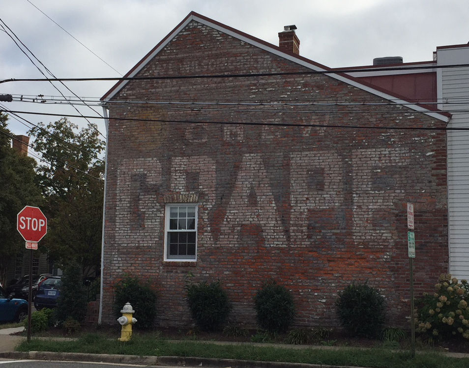 """The """"Chew Grape"""" sign in Alexandria (601 S. St. Asaph St.) emerged when plaster was removed from the side of a rowhouse. (WTOP/Jack Pointer)"""