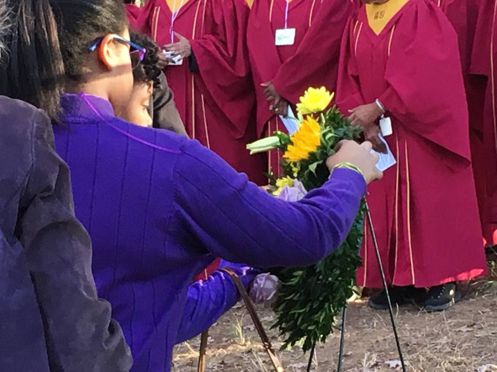 In this photo from 2016, people place a wreath to honor the memory of enslaved people who were buried at a cemetry just off Route 7.  (WTOP/Liz Anderson)