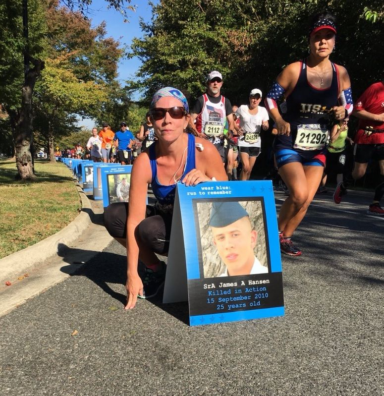 First-time Marine Corps Marathon runner poses with a photo of her cousin who died in combat seven years ago. (WTOP/Monique Blyther)