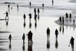People walk on the beach in Biarritz, southwestern France, Saturday, Oct. 14, 2017. Temperatures in southwestern France reached 27 degrees Celsius (80 degrees Fahrenheit). (AP Photo/Bob Edme)