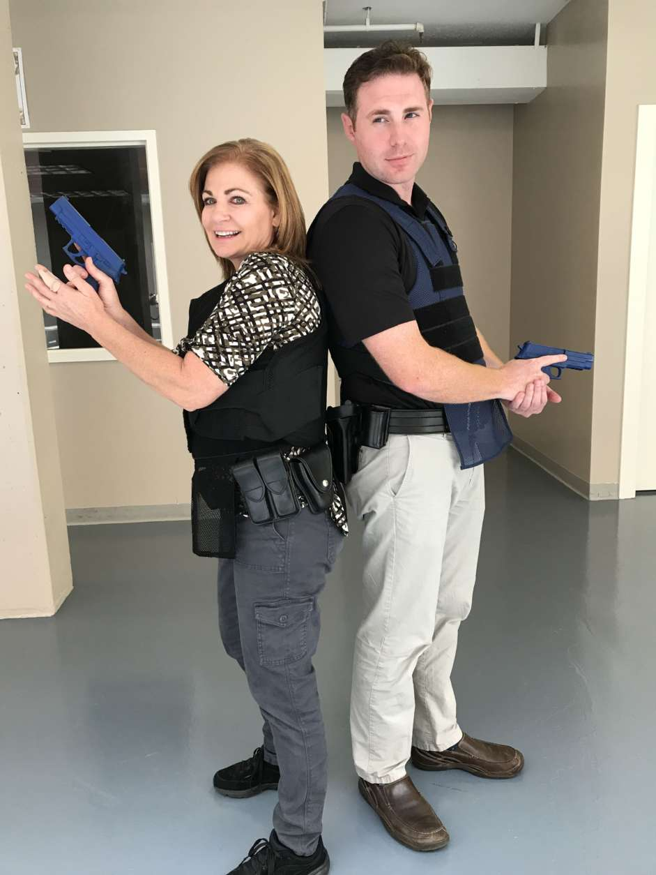 WTOP's Kathy Stewart and John Aaron pose for a picture during Fairfax County's inaugural Media Police Academy. (WTOP/Ginger Whitaker)