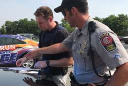 PFC Mark Pollard guides WTOP's John Aaron through the proper procedure for a traffic stop. (WTOP/Ginger Whitaker)