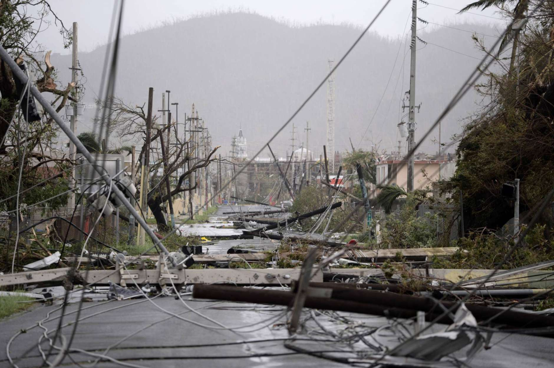 FILE - This Sept. 20, 2017 file photo shows smashed poles and snarled power lines brought down by Hurricane Maria, in Humacao, Puerto Rico. Officials warned Maria would decimate the power company's crumbling infrastructure and force the government to rebuild dozens of communities. (AP Photo/Carlos Giusti, File)
