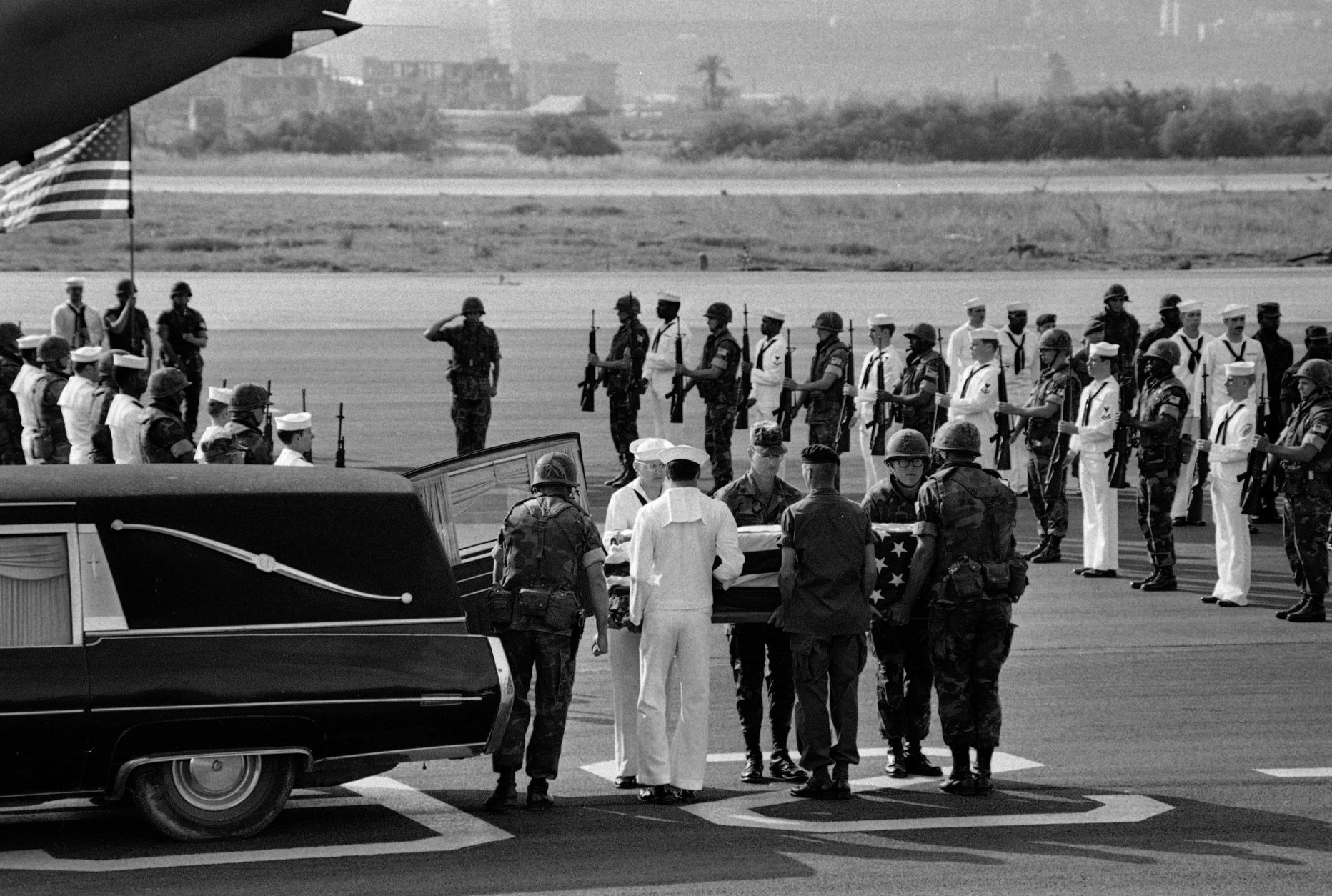 U.S. Marine and Navy pallbearers remove the coffin of one of the American staffers killed in the U.S. Embassy bomb blast in Beirut, from a hearse, April 23, 1983.  A Marine and Navy honor guard stands at attention as the bodies were then loaded on a C-141 transport plane bound for Washington.  Color guard and tail of plane are seen in the background.  (AP Photo/Zuheir Saade)