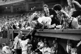 Dave Nelson of the Washington Senators shakes hands with fans before fans stopped the game by storming the field in the ninth inning in Washington, Oct. 1, 1971. The Senators forfeited the game to the New York Yankees due to fans' actions. (AP Photo/Jim Palmer)