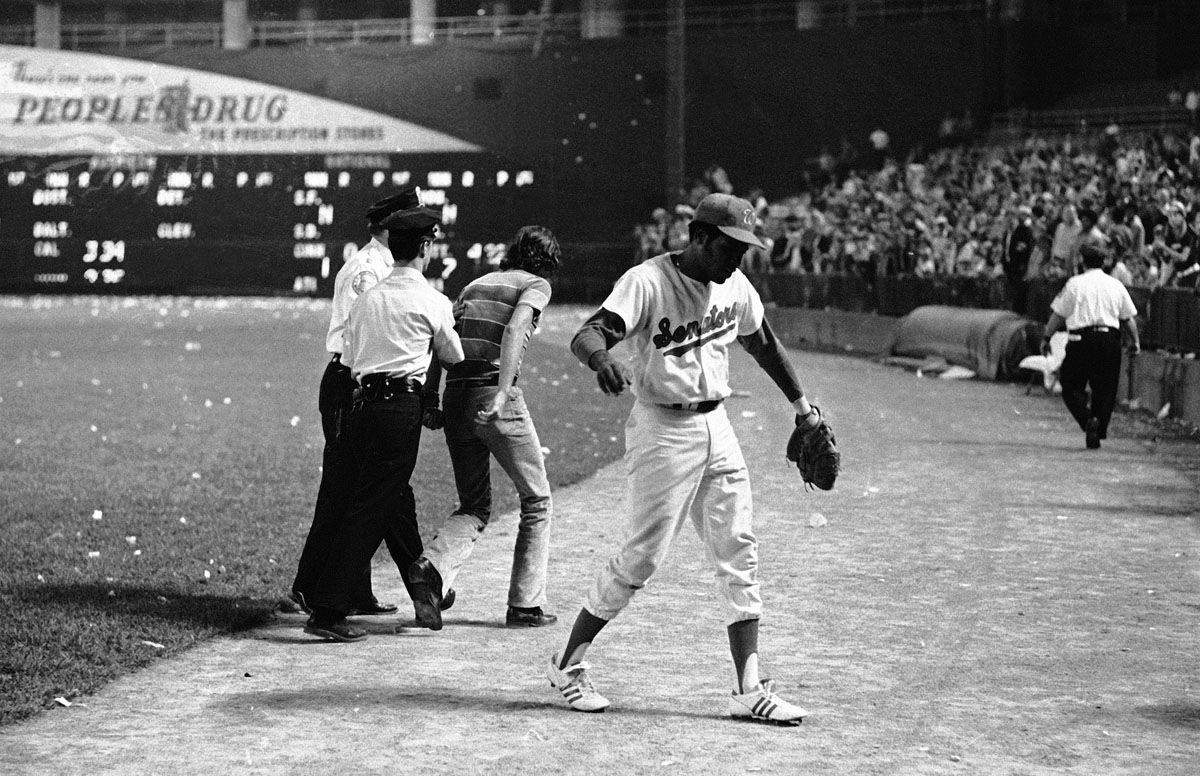 Dave Nelson of the Washington Senators makes his way toward the dugout as fans begin to storm the field in Washington, Oct. 1, 1971. The Senators forfeited the game to the Yankees due to fan actions. (AP Photo/Jim Palmer)