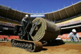 Gabriel Macedo, left, operates a lift as workers install turf on the Washington Nationals' home field at RFK Memorial Stadium, Monday, March 14, 2005, in Washington.  The playing field will have 111,000 square feet of sand-based hybrid Bermuda grass over-seeded with perennial rye grass.  Worker on the right is Raul Reyes. The first game is April 3 (AP Photo/Manuel Balce Ceneta)