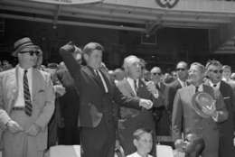 President Kennedy winds up to throw out the first ball to get things underway at the 32nd All Star game in Washington on July 10, 1962.  At right is Baseball Commissioner Ford Frick.  (AP Photo/stf)