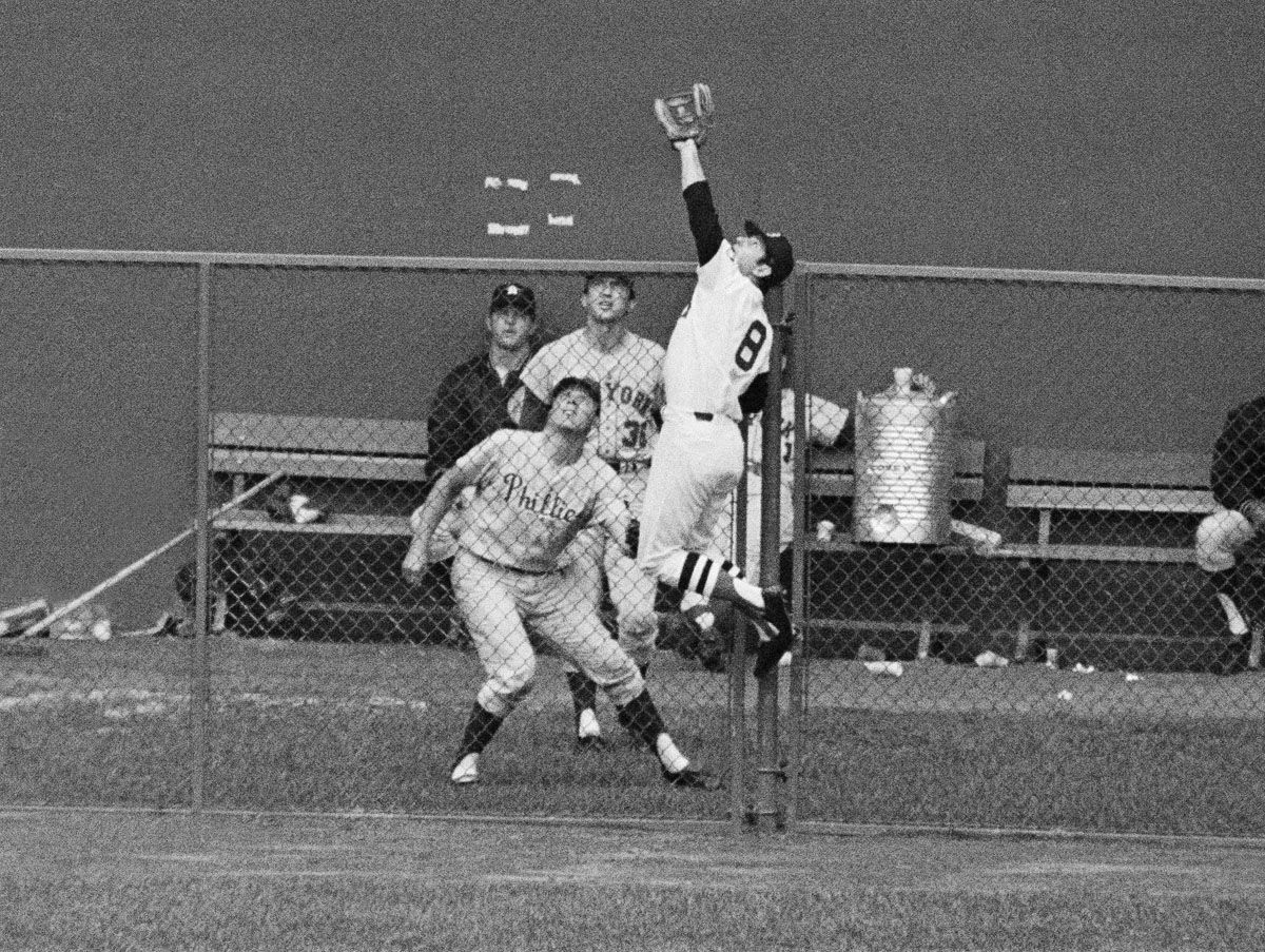 Boston?s Carl Yastrzemski of the American League leaps high over the left field fence to snag home run bound ball of National League?s Johnny Bench in the All-Star game?s sixth inning on July 23, 1969 in Washington. In bullpen are Mike Ryan, catcher, of Philadelphia and Jerry Koosman of New York, National League pitchers. (AP Photo)