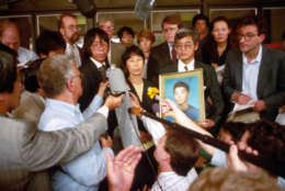 Mieko Hattori answers questions outside district court in Baton Rouge, La., as her husband Masaichi holds a photo of their slain son, Yoshihiro, following a judge's ruling in their favor Thursday, Sept. 15, 1994. The Hattori's were awarded over $600,000 in damages for the shooting death of their son by Rodney Peairs two years ago. (AP Photo/The Advocate, Bill Feig)
