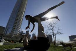 Karla Gallegos is lifted as she practices acro yoga with friends in downtown Dallas, Thursday, Feb. 11, 2016. Spring like weather has moved into Texas making being outdoors during winter enjoyable. (AP Photo/LM Otero)