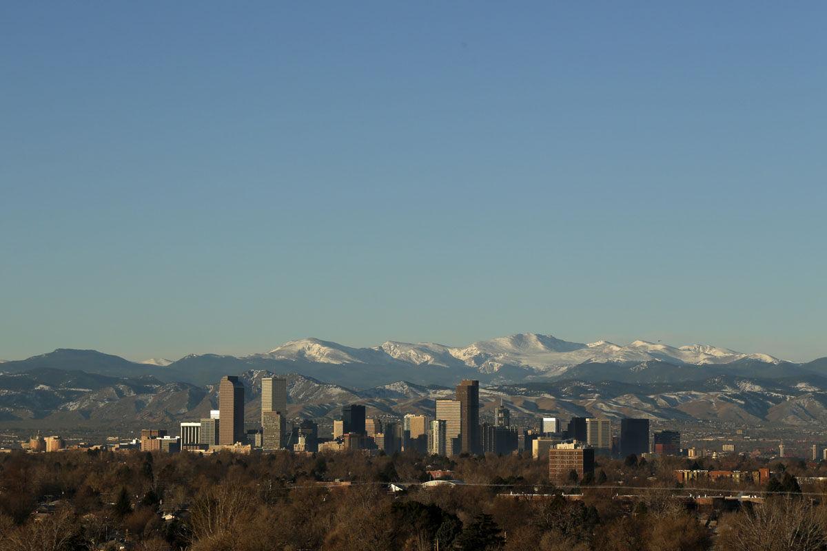 The Rocky Mountains rise beyond Denver skyline Sunday, Jan. 24, 2016. (AP Photo/Charlie Riedel)