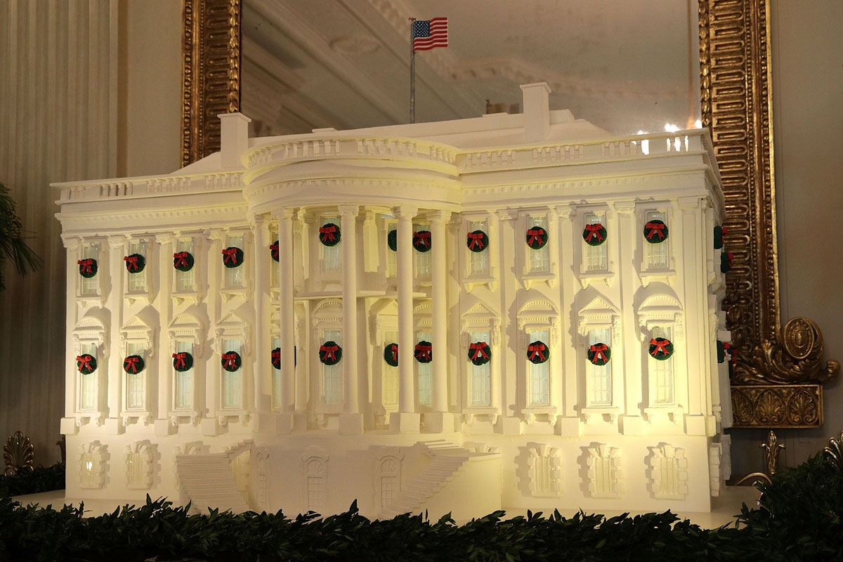 """WASHINGTON, DC - NOVEMBER 27:  The White House gingerbread house is on display in the State Dining Room at the White House during a press preview of the 2017 holiday decorations November 27, 2017 in Washington, DC. The theme of the White House holiday decorations this year is """"Time-Honored Traditions.""""  (Photo by Alex Wong/Getty Images)"""