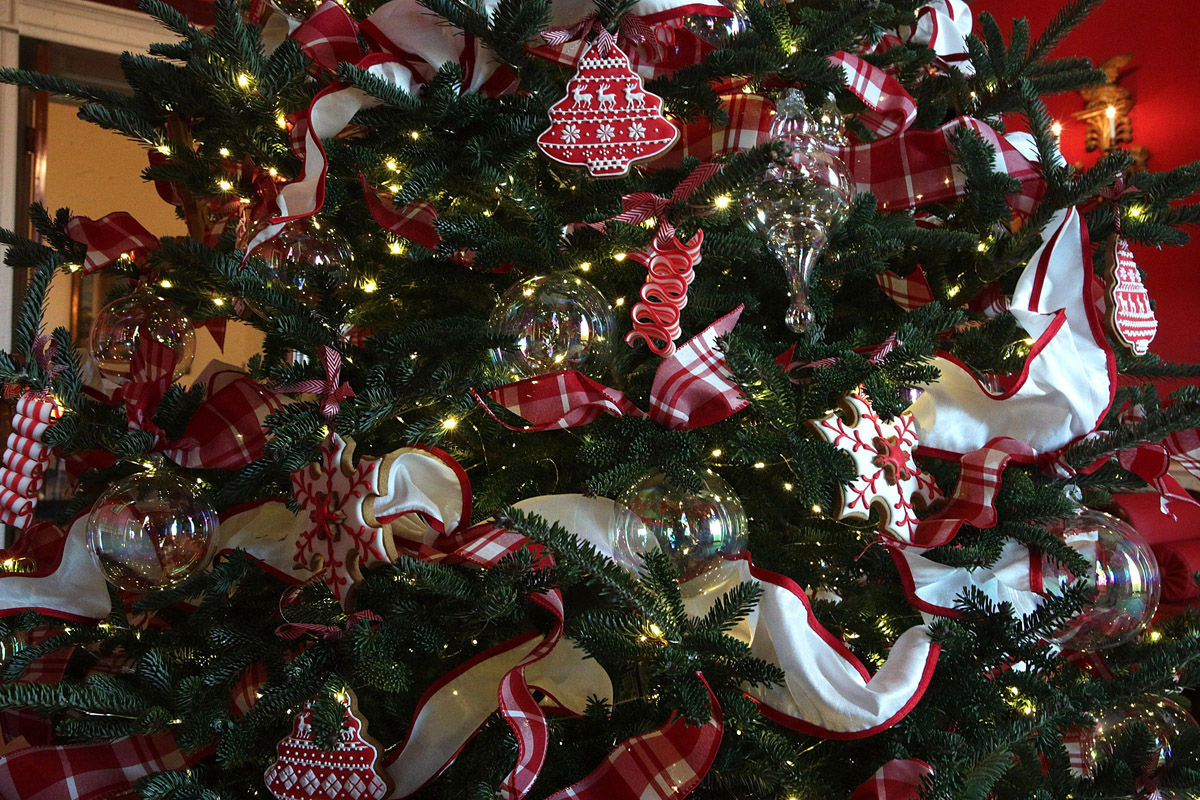 """WASHINGTON, DC - NOVEMBER 27:  Ornaments are hung on a Christmas tree in the Red Room at the White House during a press preview of the 2017 holiday decorations November 27, 2017 in Washington, DC. The theme of the White House holiday decorations this year is """"Time-Honored Traditions.""""  (Photo by Alex Wong/Getty Images)"""