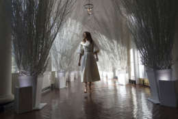 """First lady Melania Trump walks along the East Colonnade decorated in white branches that are part of 2017 holiday decorations with the theme """"Time-Honored Traditions"""" at the White House in Washington, Monday, Nov. 27, 2017.  (AP Photo/Carolyn Kaster)"""