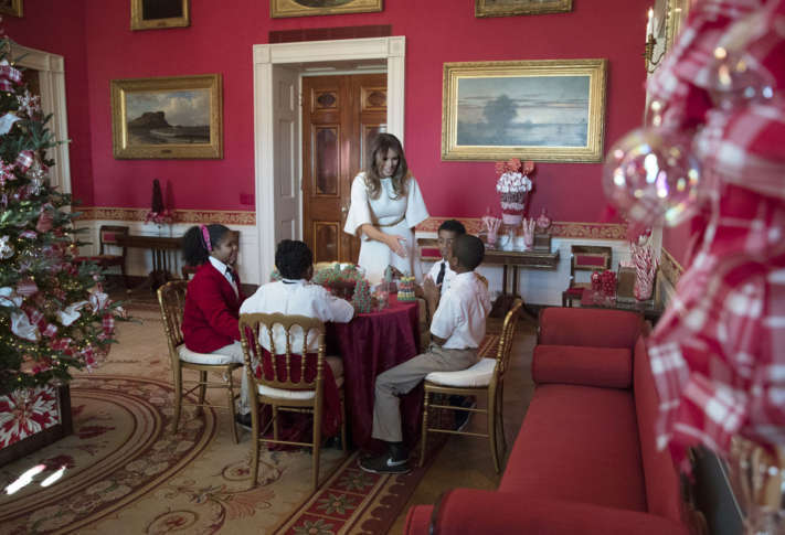 first lady melania trump visits with children in the red room working on holiday treats among the 2017 holiday decorations with the theme time honored