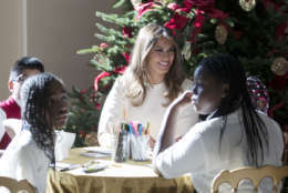 """First lady Melania Trump visits with children in the East Garden room among the 2017 holiday decorations with the theme """"Time-Honored Traditions"""" at the White House in Washington, Monday, Nov. 27, 2017. The First Lady honored 200 years of holiday traditions at the White House. (AP Photo/Carolyn Kaster)"""